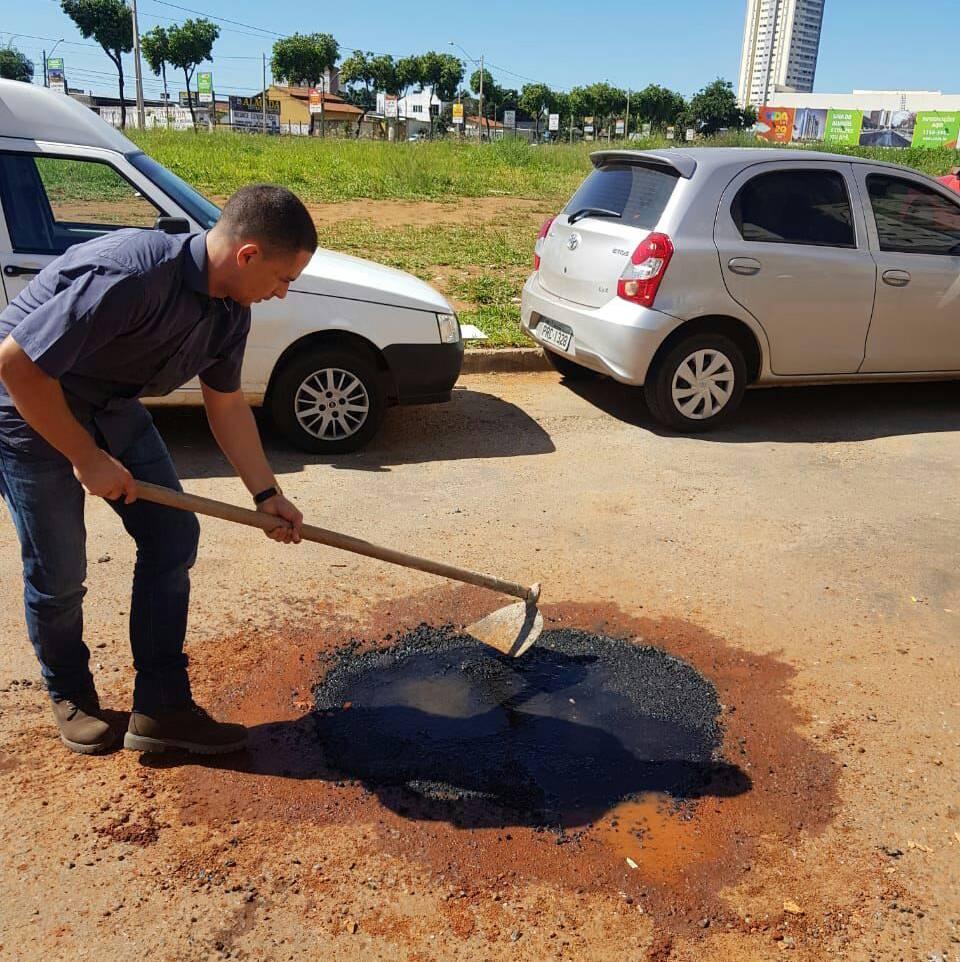 O síndico Thiago Marques, do condomínio Ilha Bela, realizando remendos de buracos da rua F-64, no setor Faiçalville | Foto: Divulgação